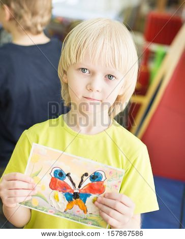 Portrait Of Cheerful Smiling Boy Holding A Bright Colorful Picture Of Butterfly Painted Colors And C