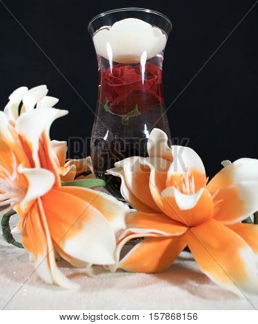 A cocktail glass with a floating rose and a white candle. The glass is on the sand.