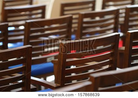 Many empty wooden chairs with backrest standing In neat rows in large auditorium.