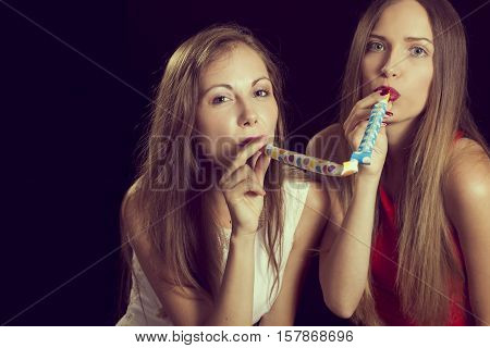 Two beautiful girls having fun at New Year's party dancing and blowing party whistles. Focus on the girl on the left