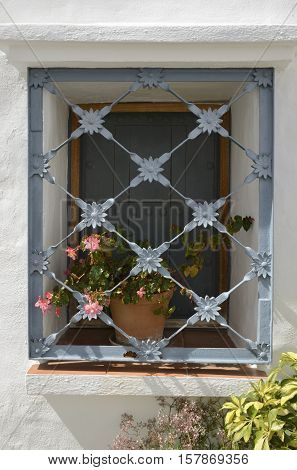 Iron bars in window with flowers pot in Ojen Andalucia Spain