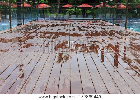 Wet outdoor floor/decking beside swimming pool after raining