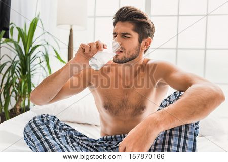 What a terrible hangover. Desperate young man is drinking water with dissolving pill. He is sitting on bed in morning