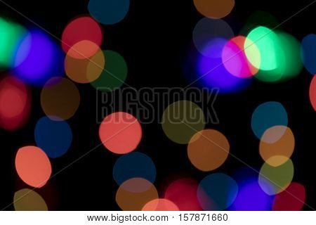 Bokeh vague colorful scattered celebration christmas lights on black background