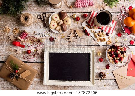 Christmas composition. Picture frame. Bowl with dried fruit, cranberries and nuts. Cup of coffee and cookies. Tangerines on plate. Christmas present and decorations. Various objects laid on table. Studio shot, wooden background. Copy space.