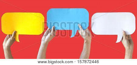 Human Hands Holding Yellow, Blue And White Speech Bubbles Over Light Orange Red Background - Fun Bal