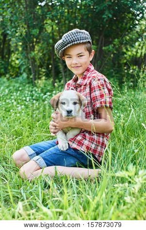 Portrait of a smiling boy with a puppy in her arms sitting on grass