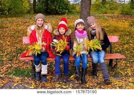 Group Of Girls In Autumn Park On The Brench