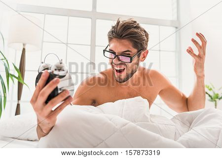 What time is it. Handsome man is holding clock and understanding that he is totally late. He is feeling furious