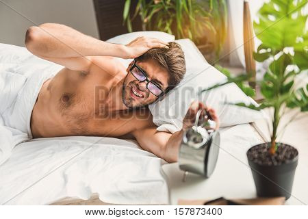 Guy is lying on bed. Man is stretching his hand to alarm-clock and beholding that he is late. He feels pain in head