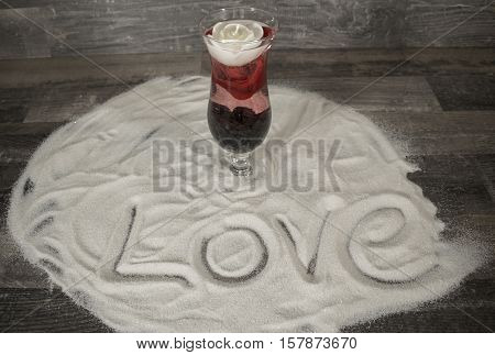 A cocktail glass with a floating rose and a white candle in the sand. There is the word love in the sand.