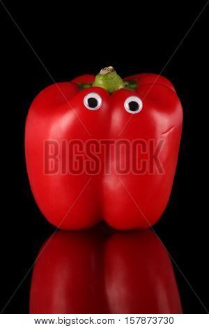 Red bell pepper with comical eyes on a black background and reflective surface.