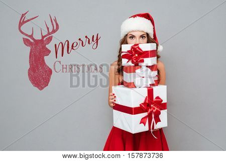 Girl hiding behind christmas gifts. Santa's helper. Dress and Santa's hat