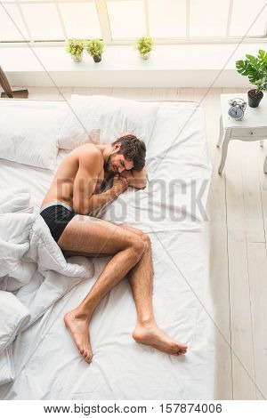 Young man is suffering from pain. He is lying on bed and closed eyes with despair. Top view