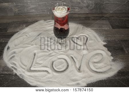 A cocktail glass with a floating rose blossom and a white candle in the sand. In the sand stands the word Love and a heart