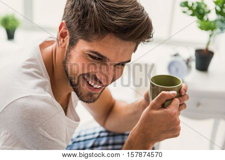 Lovely young guy is sitting on bed and holding cup. He is smiling and looking forward pensively