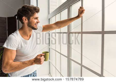Happy young man is enjoying morning at home. He is standing and looking through window dreamingly. Man is holding cup of coffee and smiling