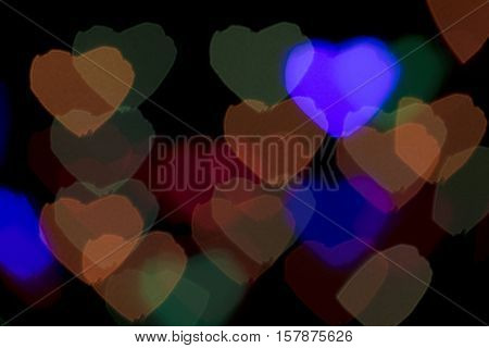 Bokeh vague colorful heart shaped big scattered celebration lights on black background