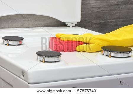 Hand In Yellow Glove Cleaning White Stove With Pink Sponge