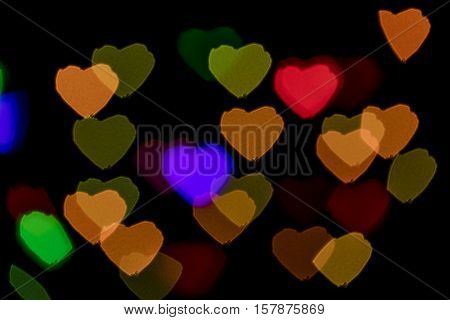 Bokeh vague colorful heart shaped scattered celebration lights on black background
