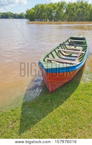A wood boat stopped on grass with Rio Pardo river in background