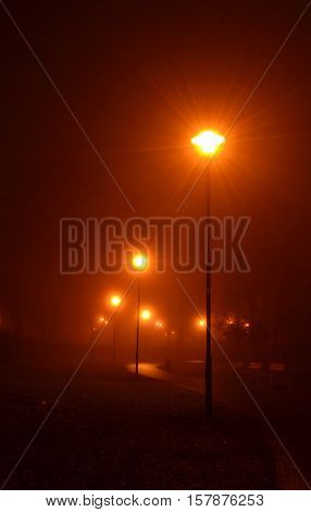 Lamppost in the park have a touch of red color and shines into the ubiquitous fog.