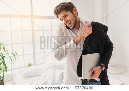 Late for a meeting. Nervous businessman is talking on mobile phone with despair. He is standing and wearing jacket in a hurry. Man is carrying laptop