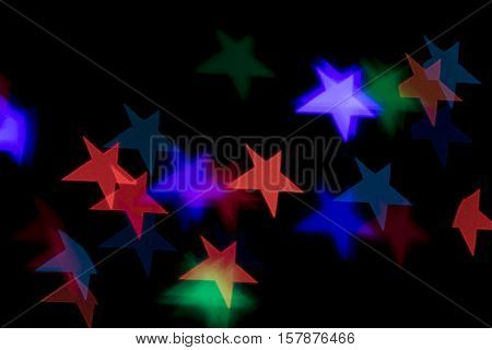 Bokeh vague colorful star shaped scattered celebration lights on black background