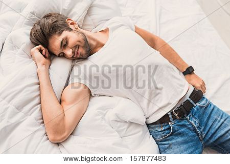 Finally rest. Top view of happy young man lying on bed with relaxation and smiling. His eyes are closed with pleasure