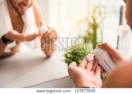 Close up of young man preparing for shaving. He is squeezing foam on fingers