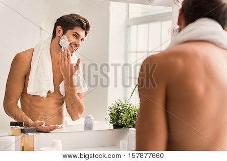 Joyful young man is applying shaving foam on his beard. He is looking at mirror and smiling