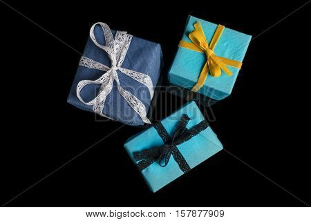 Three presents of different sizes wrapped in blue and turquoise textured paper tied with lace and velvet ribbons on black directly from above