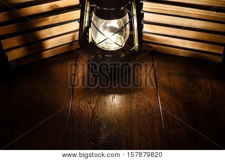 The light of a kerosene lamp and books on the table