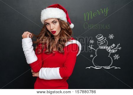 Mystery Mrs. Santa looking at the camera isolated on a black background