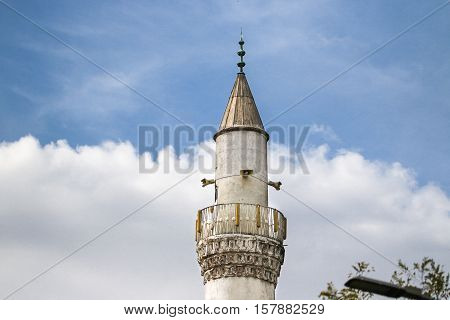 The top of the minaret of the mosque against the cloudy blue sky.