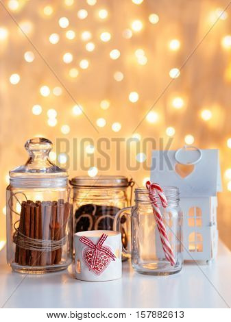 White Christmas decor over led lights bokeh. Cinnamon sticks and dried citrus in glass jars. Winter mood, holiday decoration.
