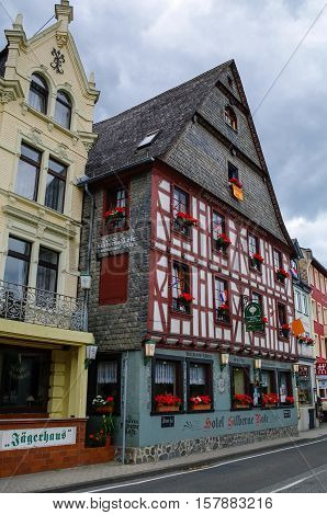 Sankt Goar, Germany - July 8, 2011: Houses on Rhine embankment in medieval village of Sankt Goar with Rheinfels Castle Germany. Rhine Valley is UNESCO World Heritage Site.