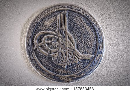 The tughra symbol is a monogram seal or signiture of a sultan from the ottoman empire. This one is situated at the Fatith mosque in Side Turkey.