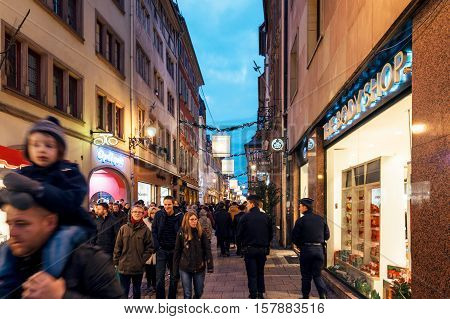 STRASBOURG FRANCE - DEC 06 2015: Police surveilling as people walking on Christmas street with shopping store opened for clients and tourist to buy presents and gifts for the upcoming holiday