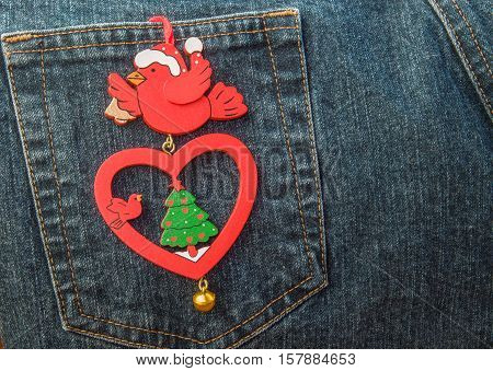 Vintage wooden Christmas bauble in shape of bird with heart hanging on back pocket of jeans.