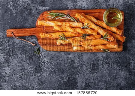 Grissini bread sticks on wooden cutting board over concrete textured surface. Top view copy space.