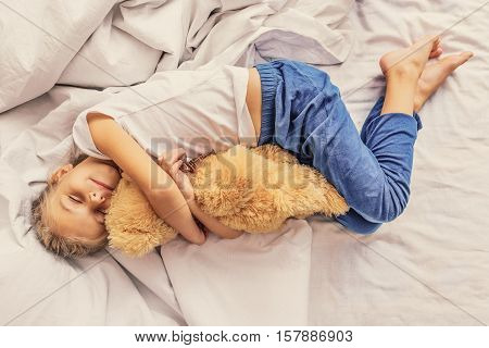 My favorite plaything. Top view of adorable little child girl sleeping in bed with her toy