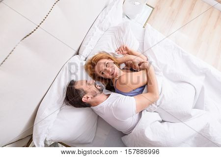 Sensitive touch.Top view of cute smiling mature couple laughing and snuggling playfully on their bed at home