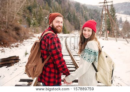Smiling couple walking on railway and looking back at camera