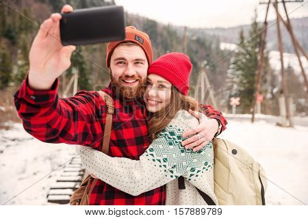 Happy couple making selfie photo outdoors