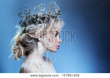 beautiful girl in the image of the Snow Queen. Clean skin white hair a crown on his head. Photographed in the studio.