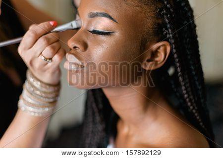 Make up of american black model. Preparing to shooting. Closed eyes. Braiding