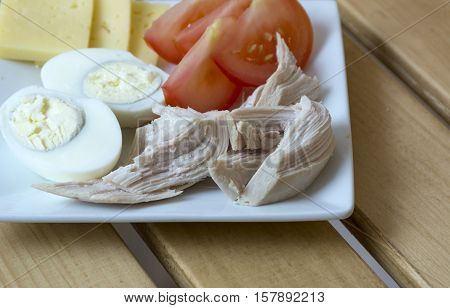 eggs boiled chicken meat sliced red tomatoes slices of cheese Breakfast healthy protein meal food