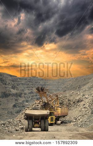 Heavy mining dump trucks are being loaded with iron ore on the opencast mining on stormy sunset