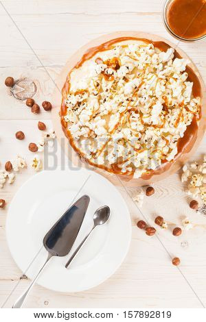 Homemade cake with hazelnuts and salty caramel with vanilla - hazel shortcakes and delicate hazelnut cream, decorated with salty popcorn. Top view.